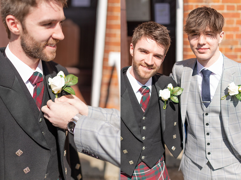 someone is straightening the groom's boutonniere, groom and best man smile at the camera before the wedding ceremony