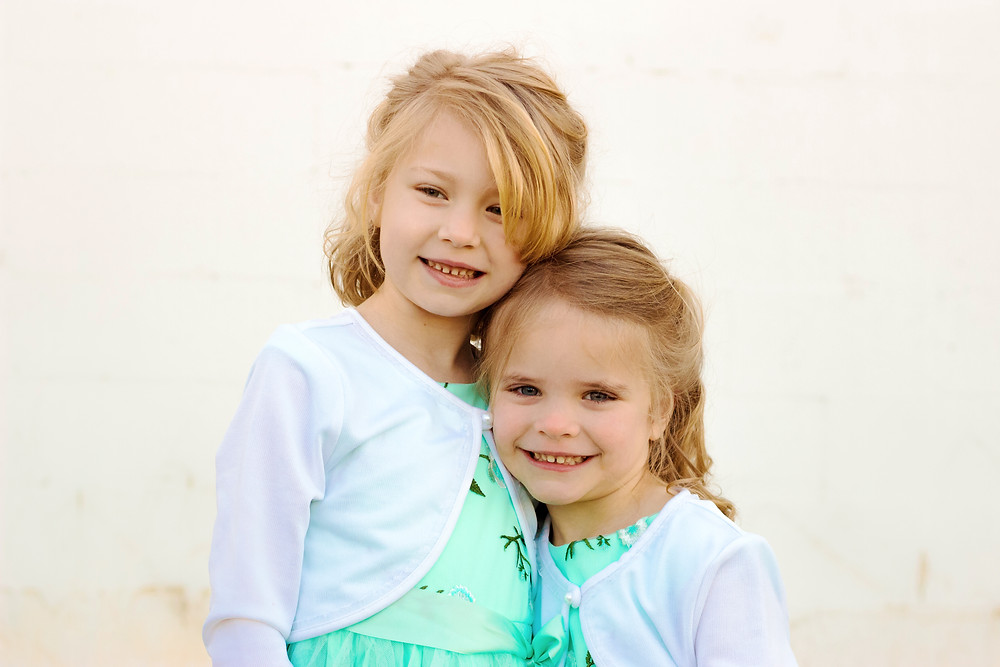 Two little girls wear matching dresses and smile at the camera