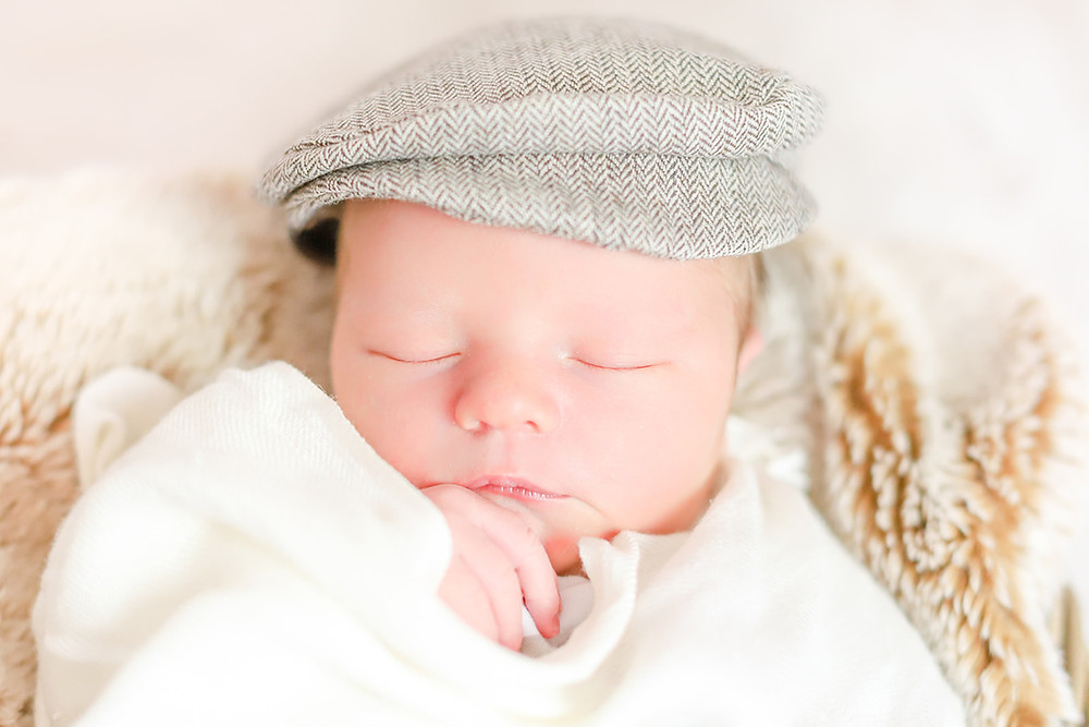 Newborn baby boy swaddled in a cream wrap and wearing a flat cap in photoshoot with Sam and Jenna Photography