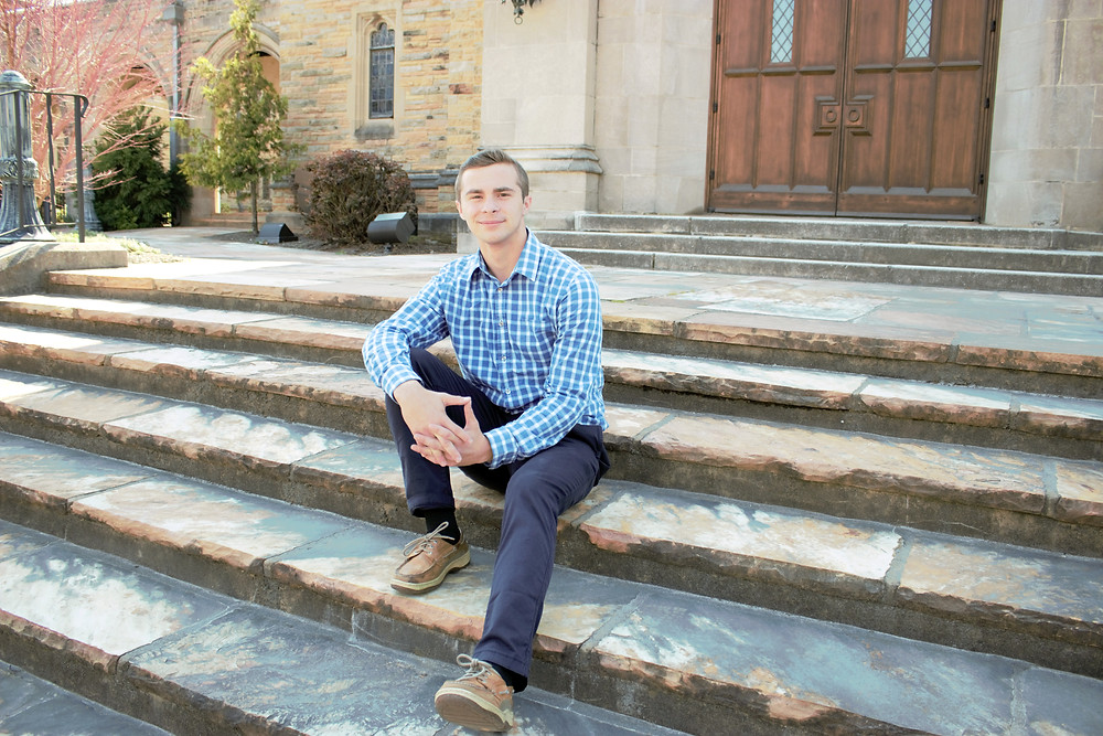 Man wearing a blue checked shirt smiles at the camera while sitting on old church stairs