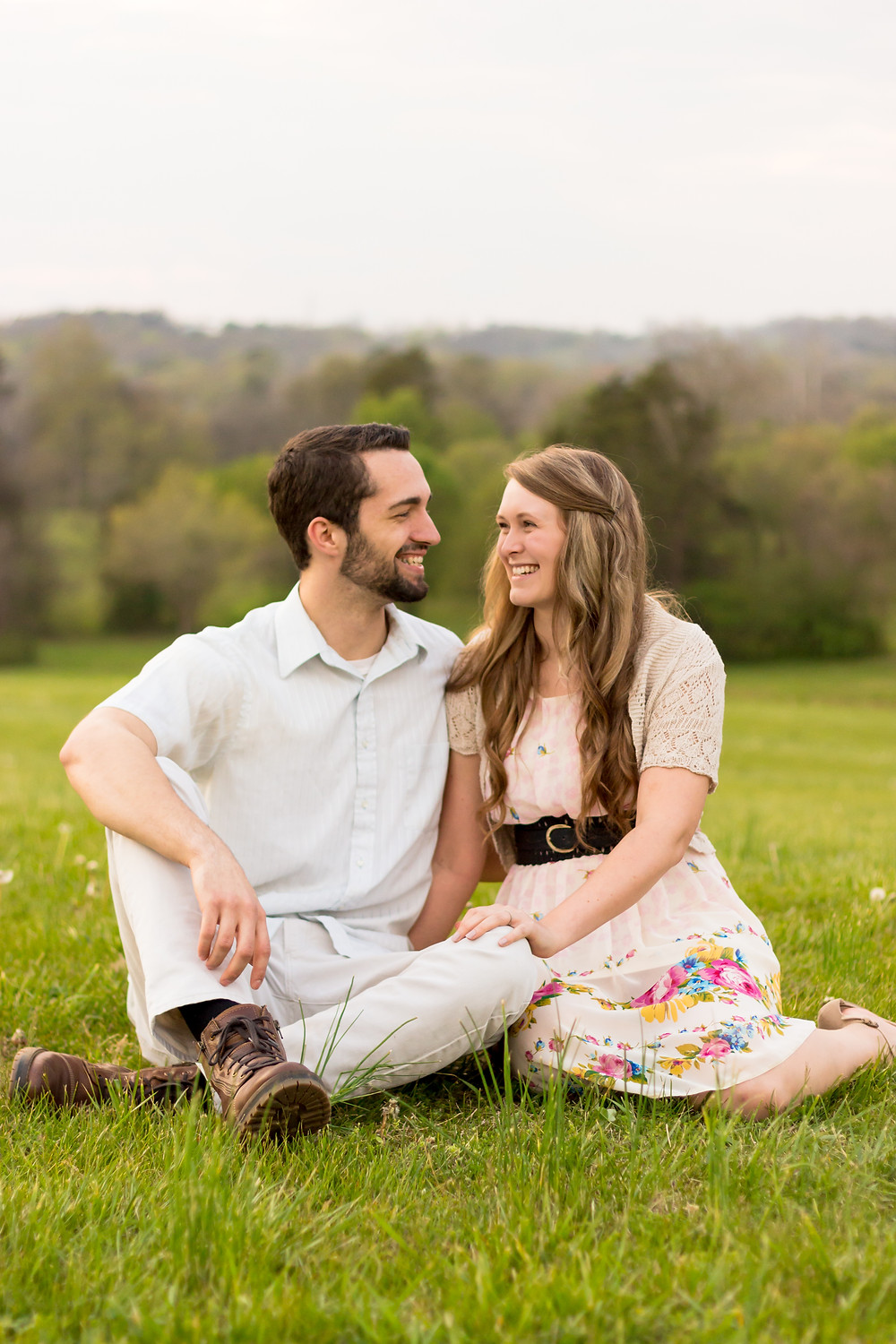 Sam and Jenna sit in a field and smile after becoming wedding photographers