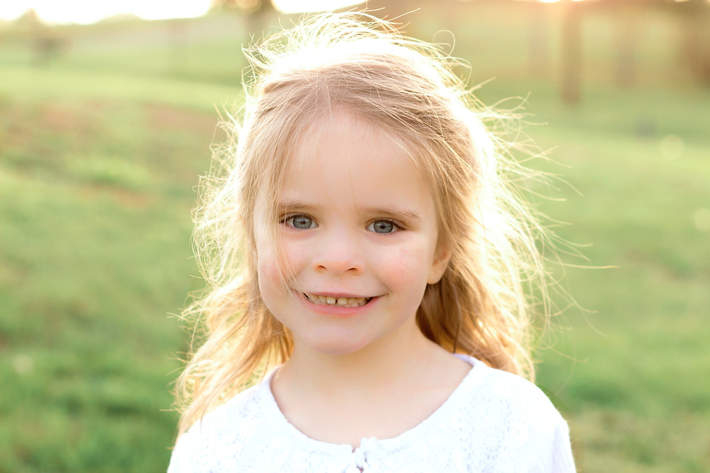 Cute little girl smiles at the camera during a photo shoot with a Devon photographer