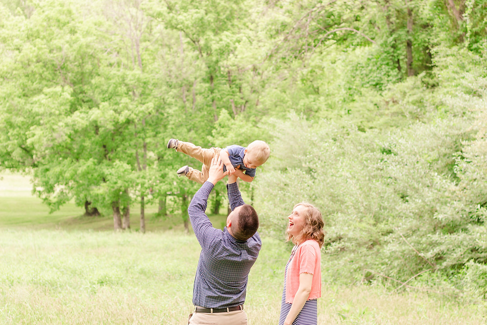 a father lifts his son in the air and mother smiles with excitement