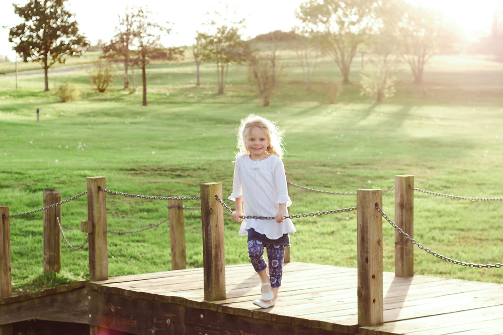 Cute little girl stands on a small wooden bridge in a park during sunset