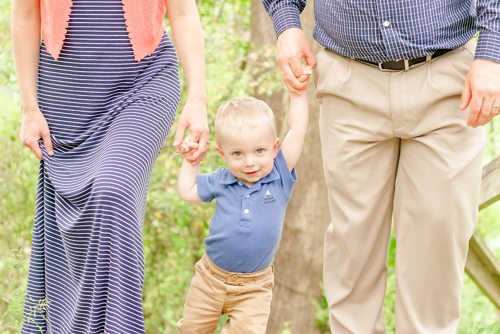 an adorable little boy smiles at the camera while his mom and dad hold his hands during a photoshoot with exeter photographers