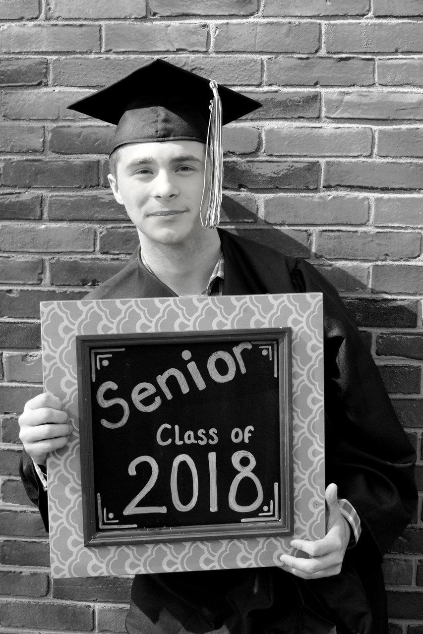 Black and white photo of a graduate in front of a brick wall taken by Exeter photographers