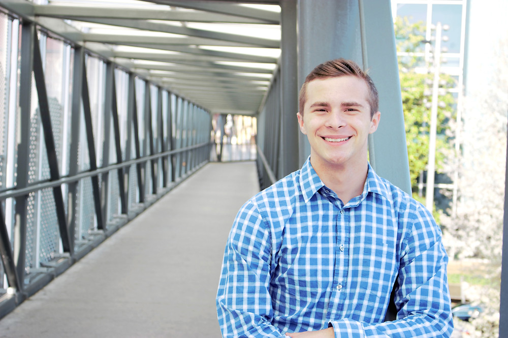 Male stands on bridge and smiles at the camera during Sam and Jenna Photographer session