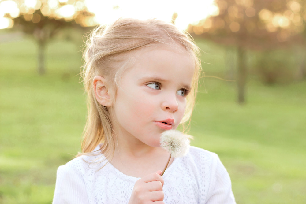An adorable little girl with blonde hair blows on a dandelion during a portrait session with Exeter photographer