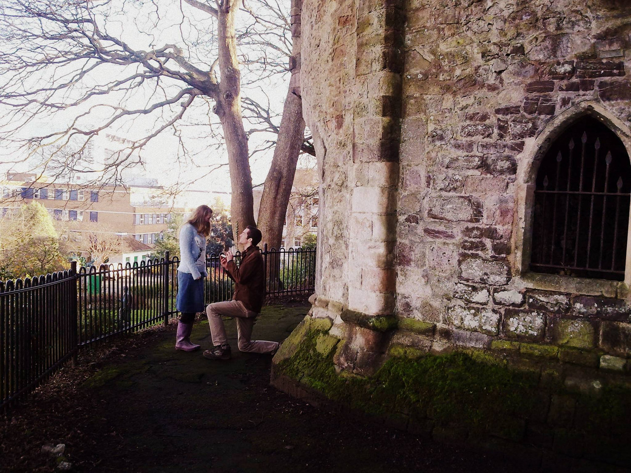 A man kneels on one knee and proposes to a girl at Rougemont Castle in Exeter, England