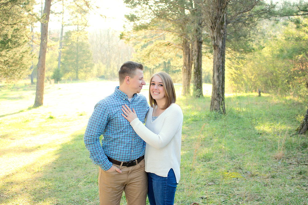 A Sam and Jenna photography couple are having their photo taken in a wooded area during sunset