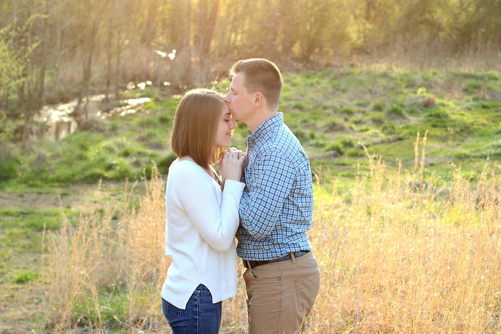 A husband kisses his wife on the head with romantic natural surroundings during a photoshoot with Sam and Jenna Photography