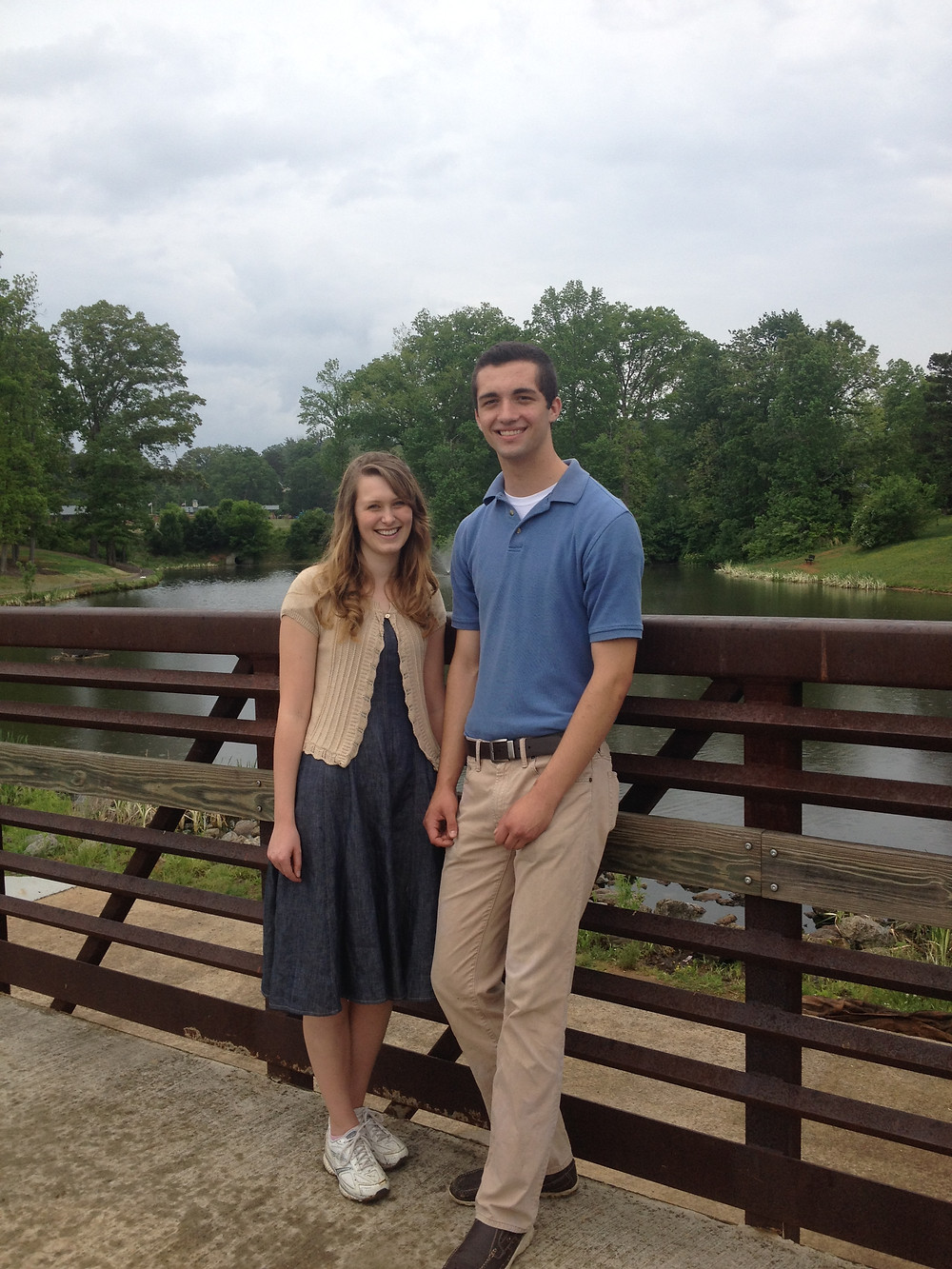 A young couple are standing on a bridge with a lake in the background