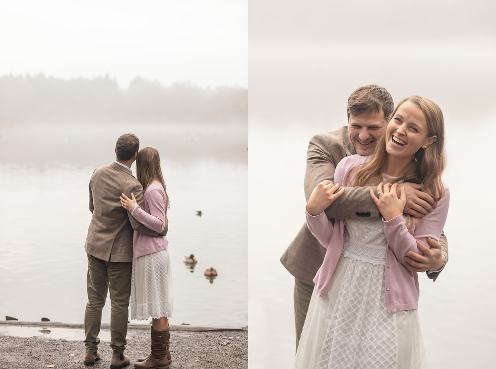 A man and woman hug and look at the ducks swimming on a misty lake.