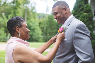 Mother of the groom puts boutonniere on groom