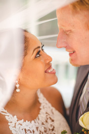 Bride and groom look into each other's eyes under veil
