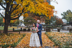 Bride and Groom posing with fall foliage in background