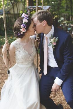 Bride and groom kissing on swings