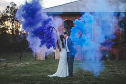 Bride and groom holding color smoke sticks and kissing at Providence Cotton Mill, North Carolina