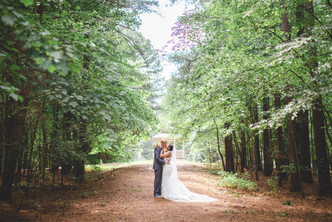 Bride and groom kiss in forest at Jetton Park