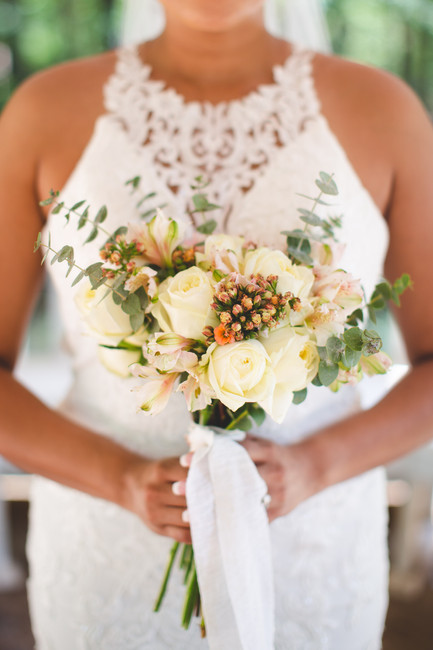 Bride holds wedding bouquet with white and orange flowers