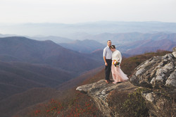 Bride and groom standing on boulder in Craggy Gardens with mountains in the background