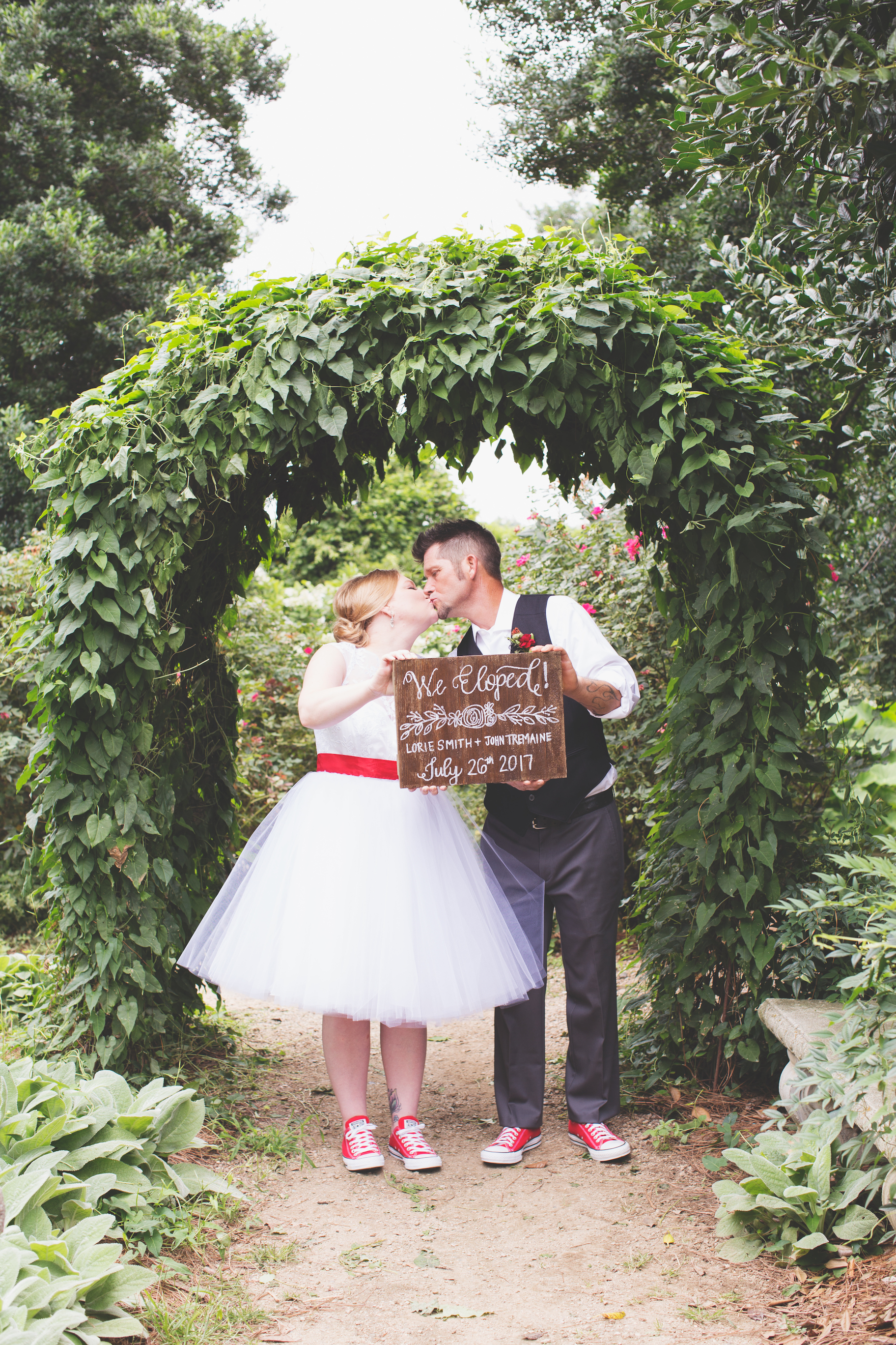 Bride and groom kissing under arch holding sign during McGill Rose Garden elopement