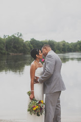 Bride and groom embrace by the Cawtawba River during their elopement at Brakefield
