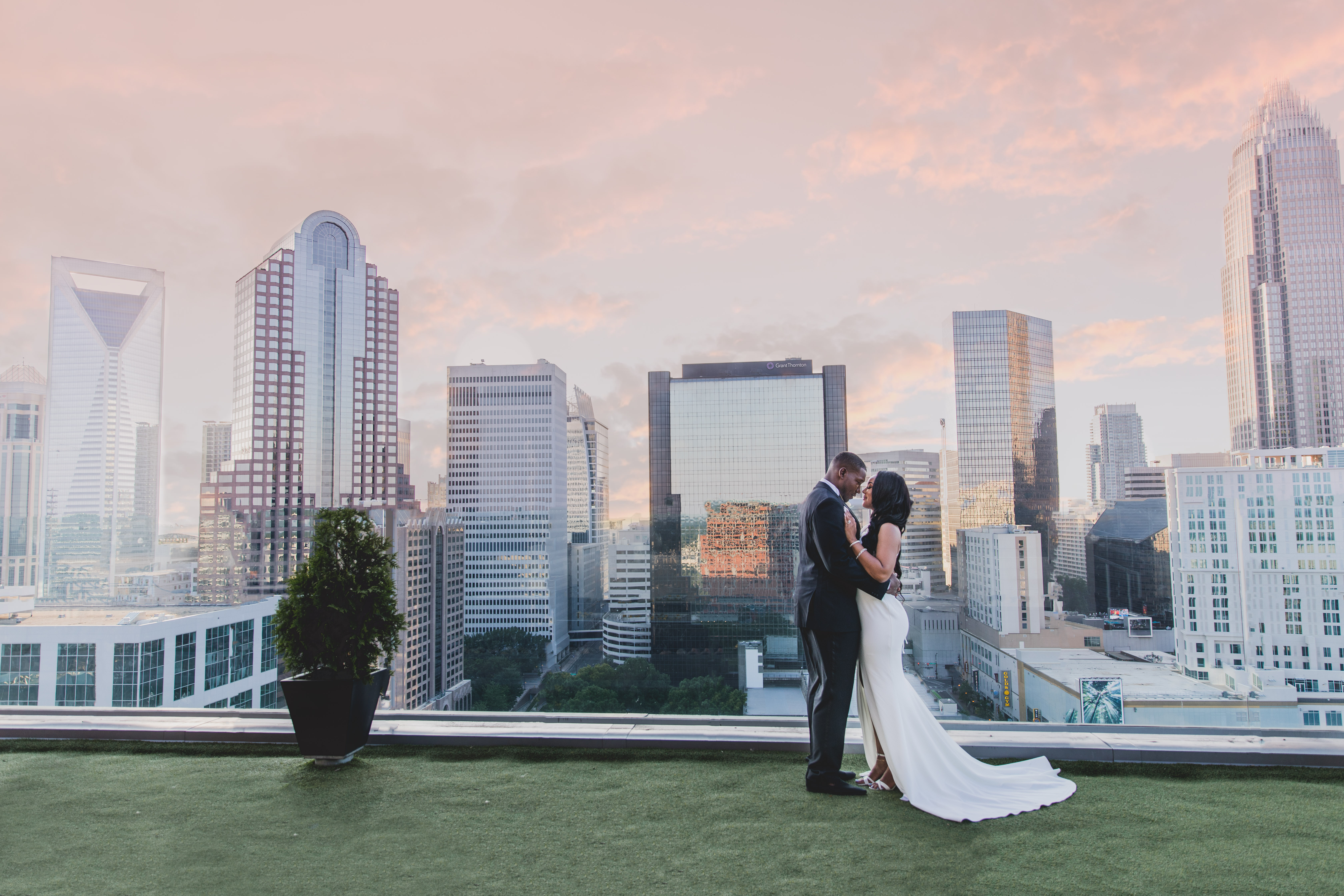 Bride and Groom embracing in front of Charlotte, NC skyline
