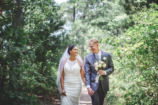 Bride and groom walk together through forest at Jetton Park