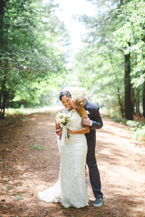 Groom kisses bride's neck in forest at Jetton Park