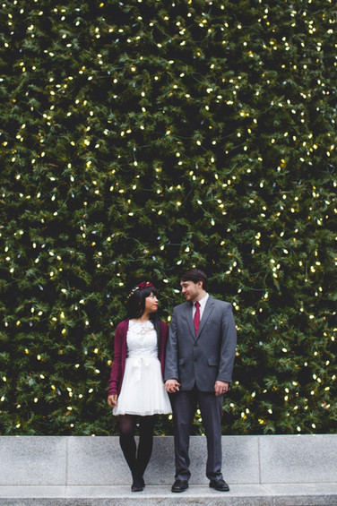 Bride and groom stand in front of holiday lights in Charlotte
