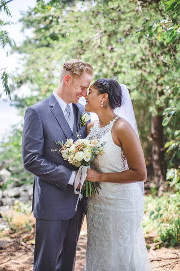 Bride and groom touch foreheads among foliage at Jetton Park