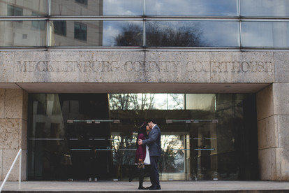 Bride and groom kiss in front of Mecklenburg County Courthouse