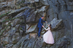Bride and Groom holding hands while climbing a rock face