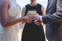 Bride places ring on groom's finger