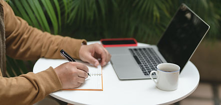 person-writing-on-white-paper-beside-mac