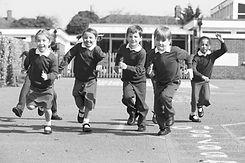 Elementary-school-students-running-in-pl
