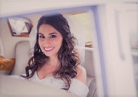 Brunette bride with curled hair in car