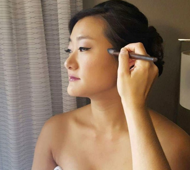 Asia woman having makeup applied.