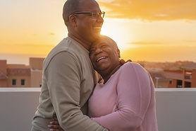 Latin senior couple having romantic moment embrac on rooftop during sunset