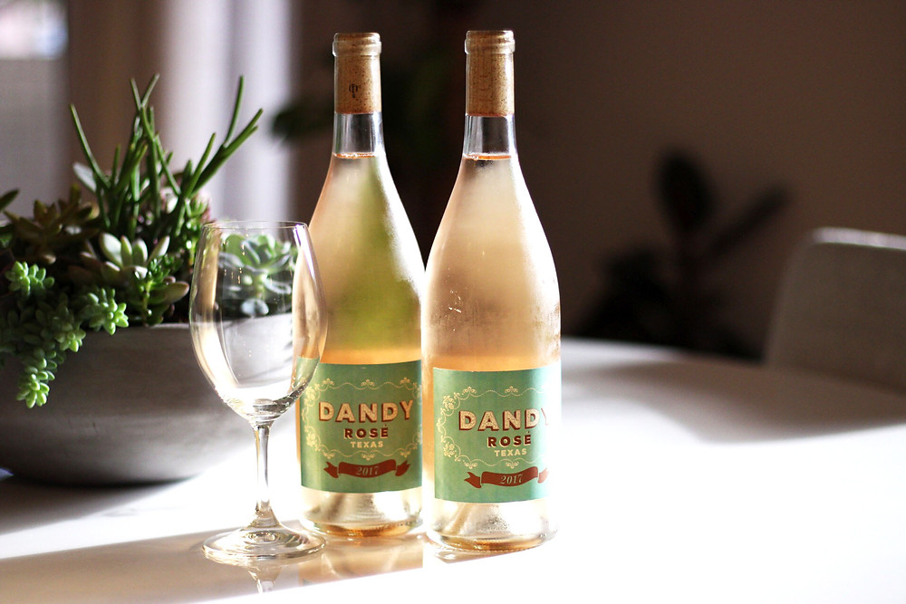 two bottles of dandy rosé wine for the people with a wine glass in front of plants