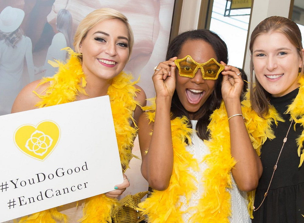 kendra scott employees wear fun yellow accessories and pose for a picture at charity event