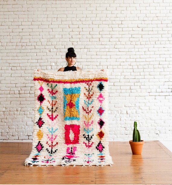 woman holding royal rug vintage rug in front of white brick wall