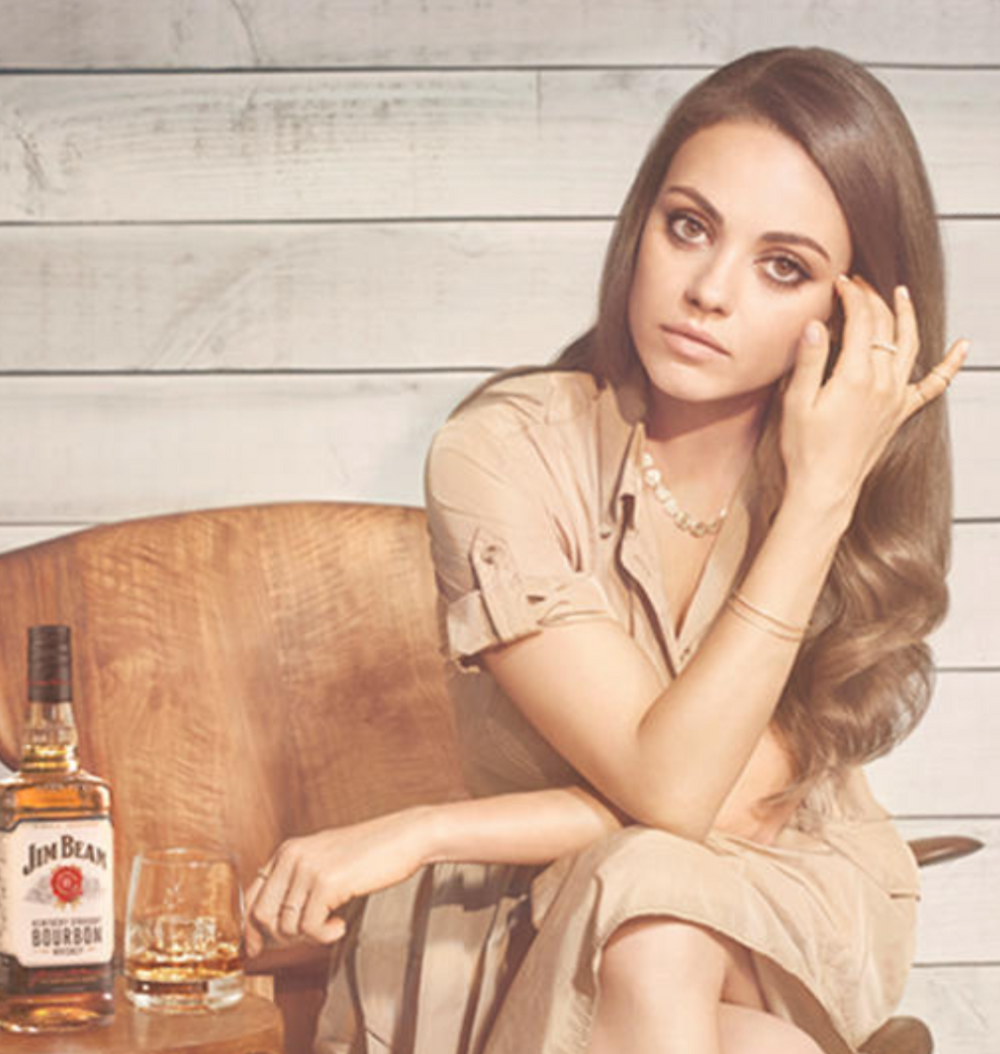 mila kunis sitting with jim bean bourbon