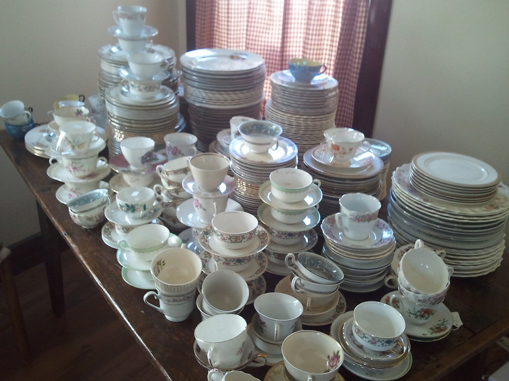 table filled with stacks of wedding event table wear and fine china