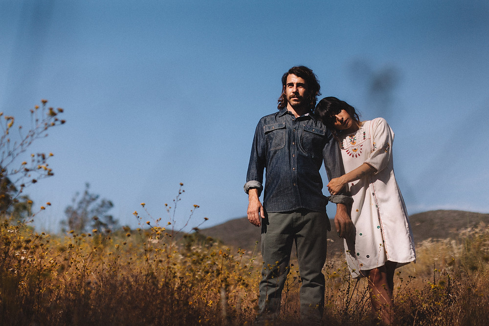 man and woman wearing denim and vintage standing in field of tall grass