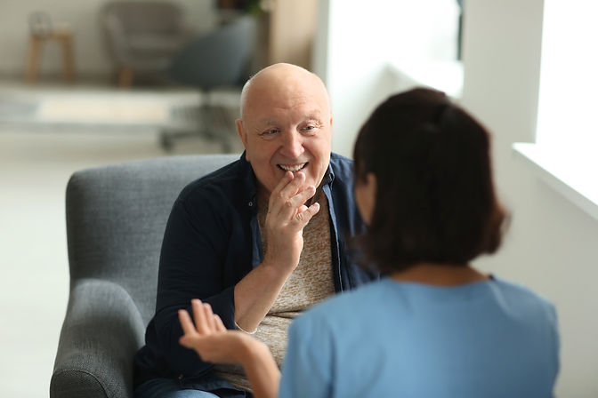Elderly man talking to a councillor and smiling