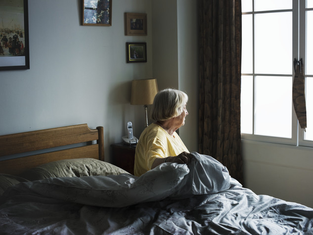 Elderly woman looking out of window in bed