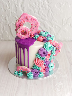 Tiny drip cake with buttercream swirls and donuts