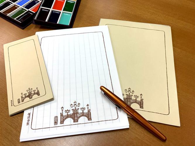 日本橋デザインの便箋はクリーム色と白色の二種類あり、一筆箋はクリーム色の一種類。 紙質にこだわり、書き心地がよいと評判。 便箋・一筆箋共に罫線下敷きタイプ(両面で縦横罫線)  便箋 価格500円+税 一筆箋 価格350円+税